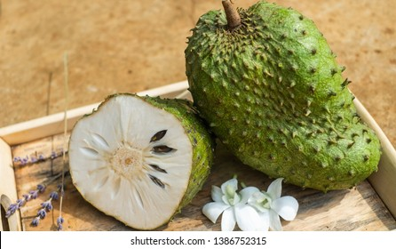 Green soursop, special fruit on the highland Dak Lak of Vietnam. One ripe soursop and one is half-sliced to show the beauty inside soursop. Fresh and tasty