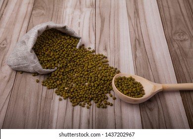 green soy mung scattered from the bag and a wooden spoon lie on a wooden background. superfood. Zero waste.