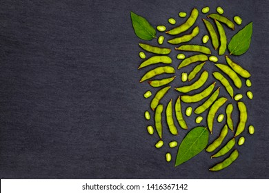 Green soybean pods on dark background. Edamame, close up. Green soy pods, beans on black stone slate surface. Green Soy on black background. Soybean on black slate