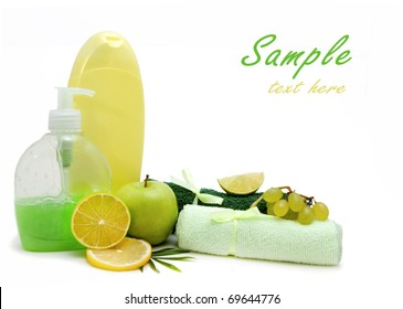Green spa composition: liquid soap, shampoo bottle, towels and fruits isolated on white background