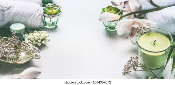 Green spa or wellness background with towels, candle, orchid flowers and body and face care tools and accessories on white desktop, top view with copy space, frame