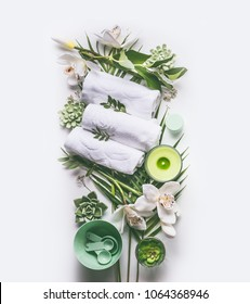 Green spa or wellness composing with towels, candle, tropical leaves , orchid flowers, succulents and body and face care tools and accessories on white background, top view
