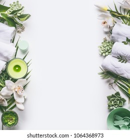 Green spa or wellness layout frame with towels, candle, tropical leaves , orchid flowers, succulents and body and face care tools and accessories on white background, top view.