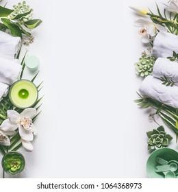 Grüner Wellness- oder Wellnessbereich mit Handtüchern, Kerze, tropischen Blättern, Orchideenblumen, Sukkulenten, Körperpflegemitteln und Accessoires auf weißem Hintergrund, Draufsicht.