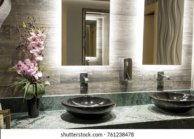 Green Special Design Marble Counter, Black Top Counter Washbasin, beautiful pink flower, chrome tap, metal soap dispenser and beige Textured Wall Tiles at Commercial Public Bathroom in Office Building