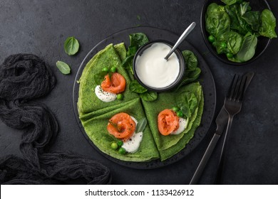 green spinach crepes with smoked salmon and yogurt sauce on black plate, dark background, top view