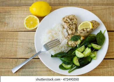 Green spinach and cucumber salad, white rice and chicken fillet baked with thyme and lemon and served on a white plate. Top view