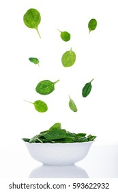 Green spinach leaves flying on white, fresh salad in motion, vegetables levitation concept