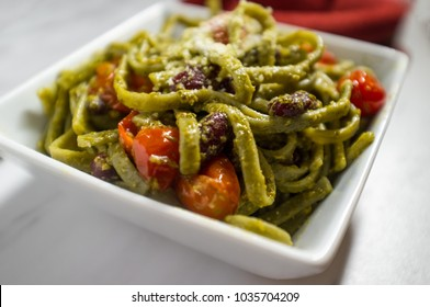 Green spinach linguine with creamy pesto sauce kidney beans and grape tomatoes