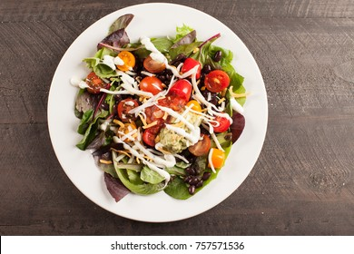 Green spinach salad with chopped red and orange tomato, black beans, shredded cheese, avocado, and salsa on a white plate horizontal shot