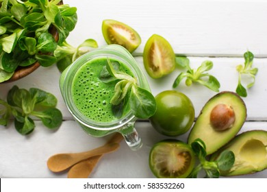 Green spinach smoothie with fresh leaves in jar on white wooden background. Top view. Healthy diet gluten free concept