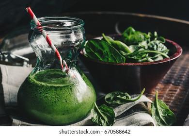 Green spinach smoothie on dark background