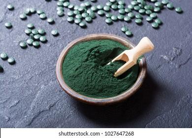 Green spirulina powder in bowl and pills . nature medicine