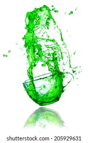 green splashes out drink from glass on a white background.
