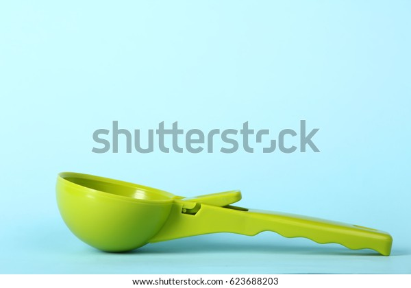 Green spoon for ice cream on a blue background