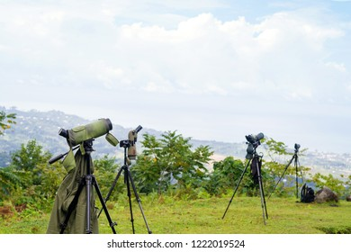 Green spotting scope or monocular at mountain top against the background of a mountain landscape in summer day. Observation of birds, birdwatching