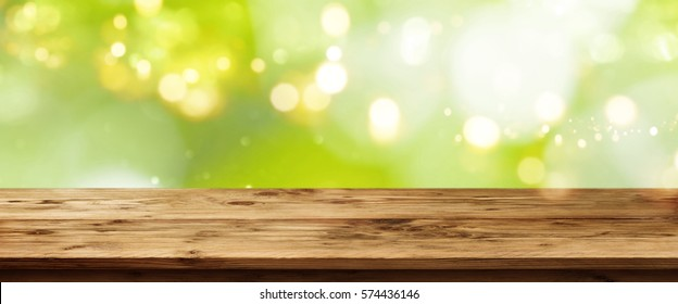 Green spring background with bokeh in front of an empty wooden table for a concept