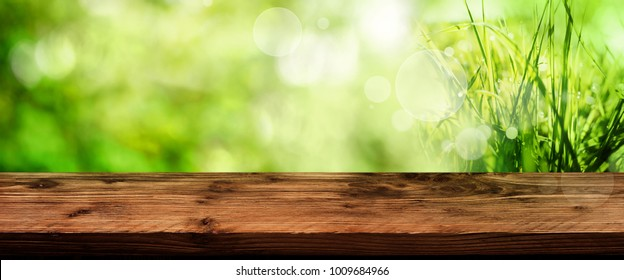 Green spring background with empty old wooden table for a easter decoration
