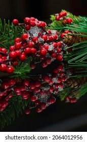 Green spruce branch with red berries on a black background. Beautiful Christmas decor, vertical photography.
