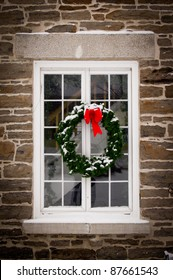 A green spruce Christmas wreath with red ribbon hangs in the middle of an old, snow covered window pane set in stone wall.