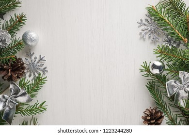 Green spruce twigs, pine cones and silver Christmas decorations on white background with copy space