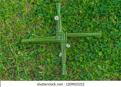 A green St. Brigid's cross, lying on a bed of clover, and daisy flowers.