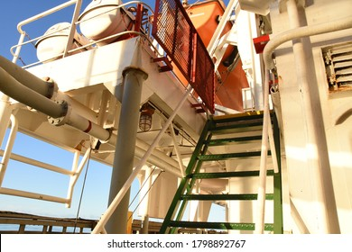 Green stairs with red protection metal security grill on top against piracy attack on container vessel. Steps leading to emergency embarkation deck and muster station with life boat and life rafts.