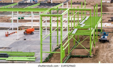 Green Steel Frame Construction on Job Site with Foundation of Concrete