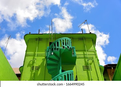 Green stone exterior spiral staircase on Singapore shophouse in historic Geylang with strong architectural detail, textures in perspective view against sky