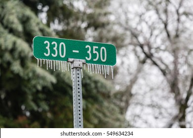 Green street address sign with hanging ice cycles from a December ice storm.