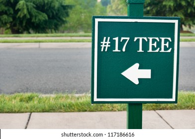 Green street sign pointing to 17th tee at golf course.