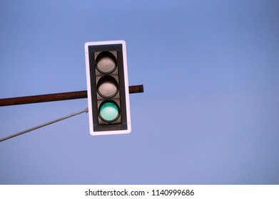 The green streetlight signal with blue skies in the background.
