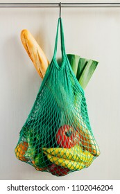 Green string shopping bag with vegetables, fruits and bread hanging on a hook in the kitchen
