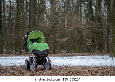 the green stroller is standing on the snowy ground in the forest with trees in the background in winter