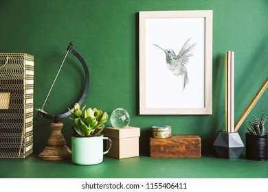 Green stylish desk with gold mock up poster frame, office accesories, boxes and design plants. Creative composition of space.