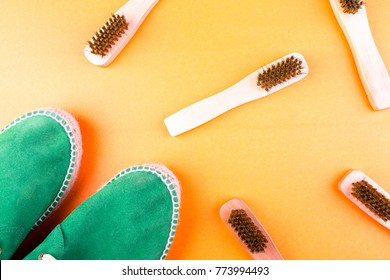 Green suede espadrille shoes with brushes on yellow paper background