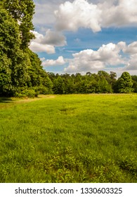 A green Summer field with blue sky and puffy clouds in this park in Monmouth County New Jersey.