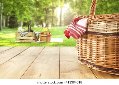 green sunny day in park and red napkin wooden table and picnic basket