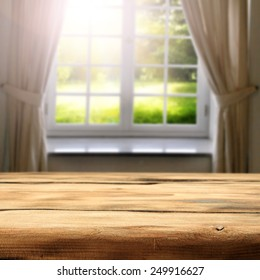 green sunny view of garden in window and desk space of wood