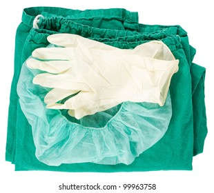 Green surgical clothing and sterile gloves over a white background