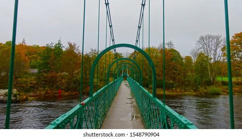 A green suspension bridge over a river in Autum