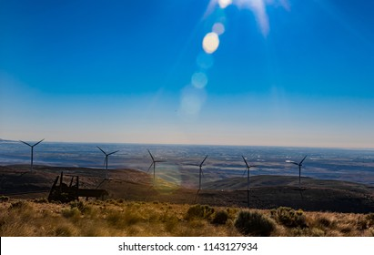 Green sustainable energy windmill power turbine electricity generators on rolling hills with clouds and blue sky above