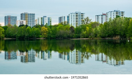 Green symmetry at lake, green trees and city buildings symmetrical reflected in lake