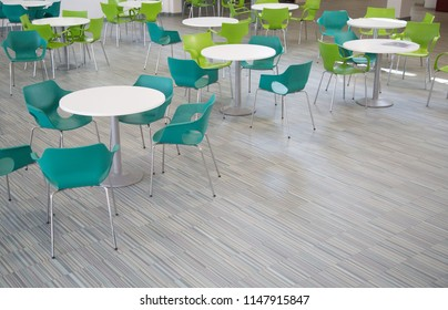 green tables and chairs in a school or college canteen or cafe.