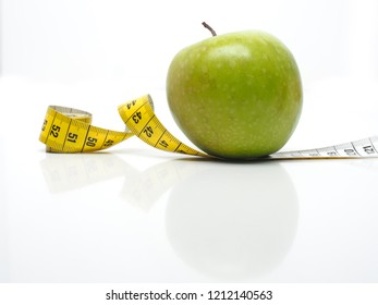 Green tasty apple with a measuring tape on a white table, diet or healthy food concept
