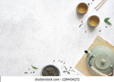 Green Tea Arrangement -  iron teapot and ceramic teacups with green tea and leaves. Traditional asian tea composition on white background, copy space, top view.
