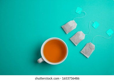 Green tea bags, next to a cup with a drink. Cup of tea on a turquoise background. Minimalistic design of tea zerimony.