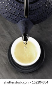 Green tea being poured out of a Japanese teapot, selective focus