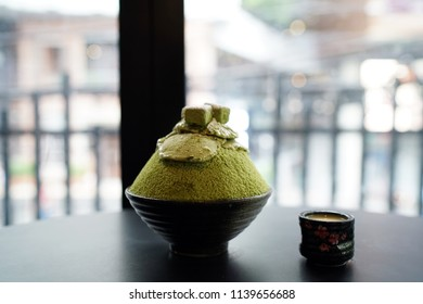 Green tea bingsu or Korean shaved ice dessert, Topped with matcha ice cream and green tea chocolate served with sweetened condensed milk on the table, same as Kakigori.