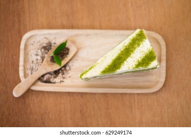 Green tea cake and spoon on wooden plate